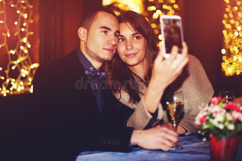Mooi paar in liefdezitting in een restaurant die een smartphone gebruiken om een selfiebeeld te nemen royalty-vrije stock afbeeldingen