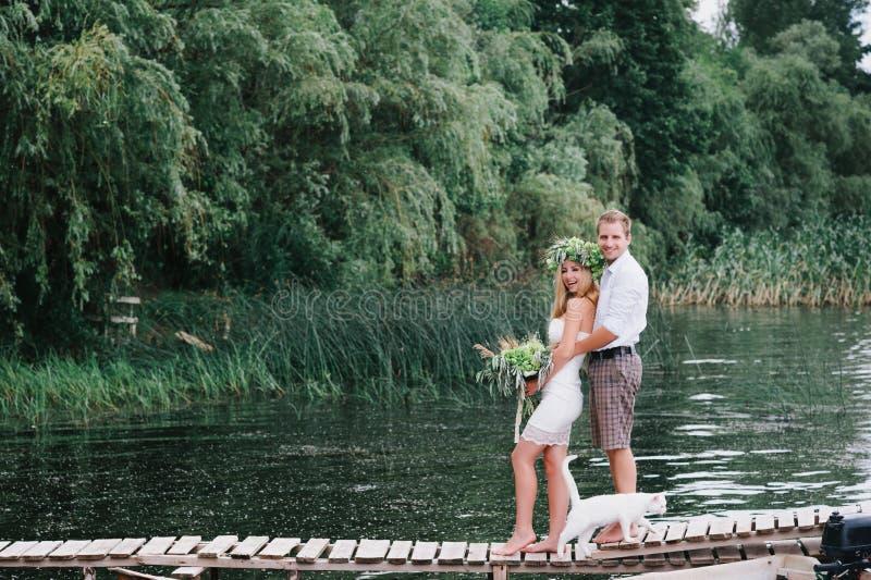 Mooi paar met een boeket op de brug met een witte kat stock foto's