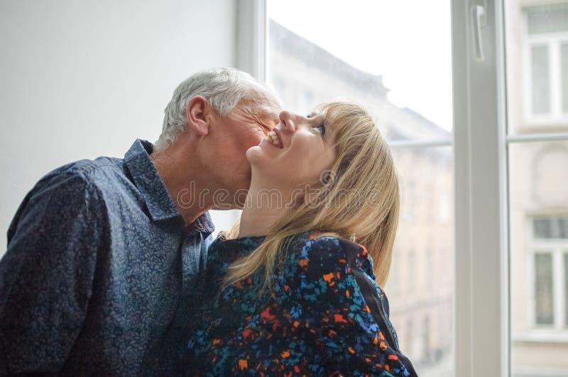 Mooi Paar met Leeftijdsverschil het Kussen dichtbij Geopend Venster binnen het Huis tijdens de Lentetijd stock afbeelding