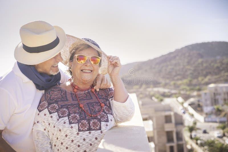 Mooi paar van hogere bejaarde volwassen mensen die en vrije tijds van openluchttijd in de zomer glimlachen genieten terrasdak met royalty-vrije stock foto