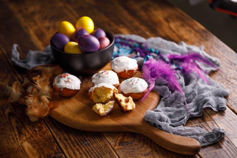 Mooi Pasen-stilleven met cupcakes en ongebruikelijk geschilderde eieren op een houten achtergrond stock afbeelding