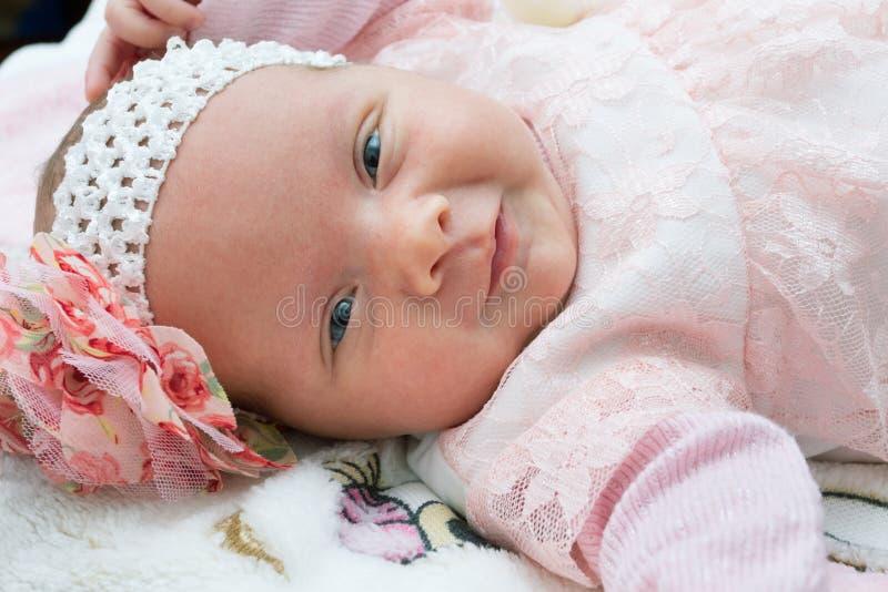 Mooi pasgeboren babymeisje met een bloem op haar hoofd die en camera glimlachen bekijken royalty-vrije stock afbeeldingen