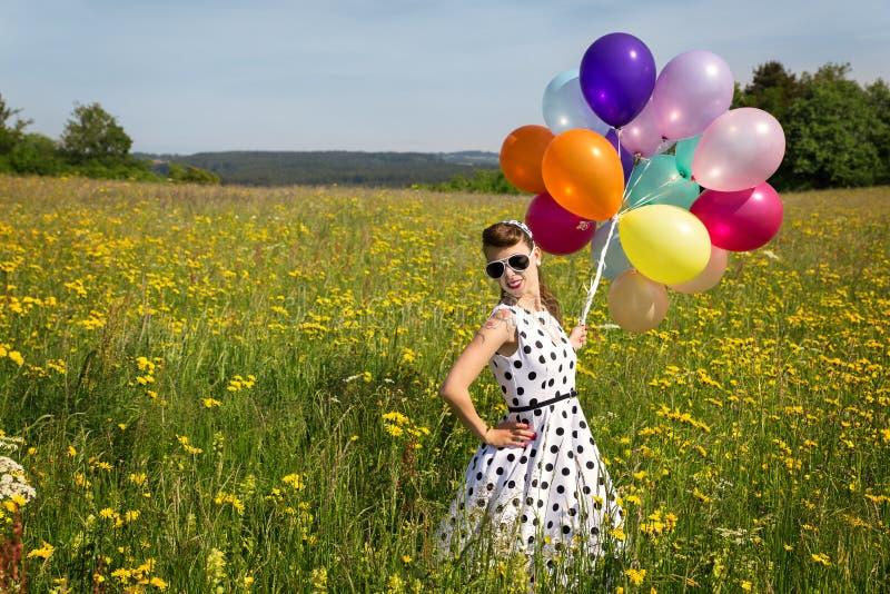 Mooi pinupmeisje met ballon op een weide royalty-vrije stock fotografie
