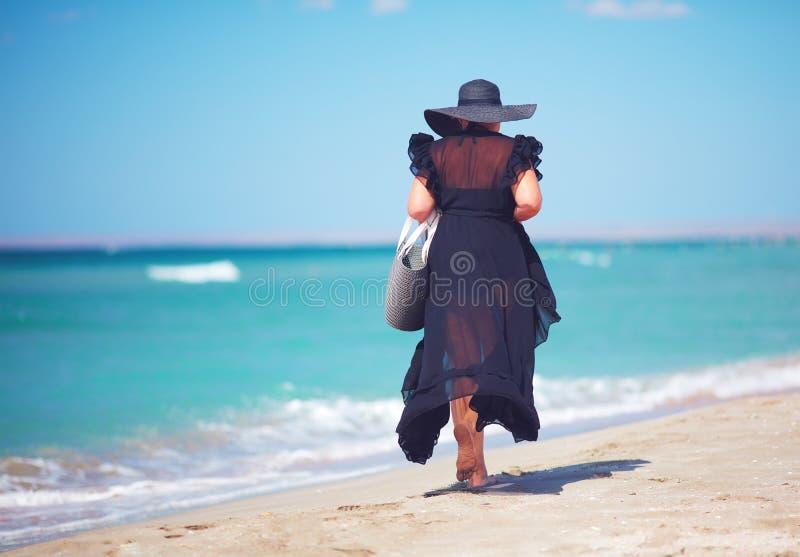 Mooi plus grootte geniet de volwassen vrouw de zomer van vakantie door langs het zandige strand te lopen stock fotografie