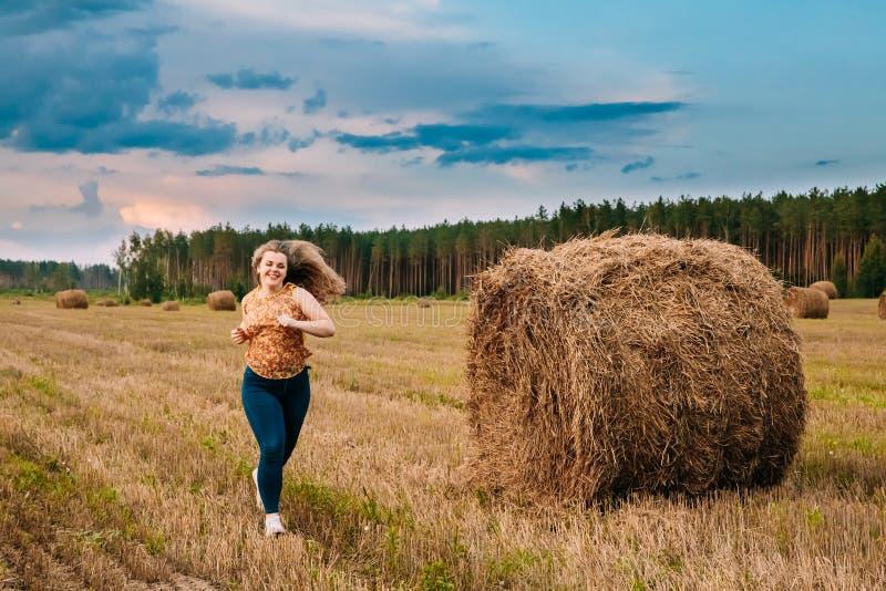 Mooi plus Grootte het Jonge Vrouw Lopen dichtbij Hay Bales In Summer Field-Weide stock foto's