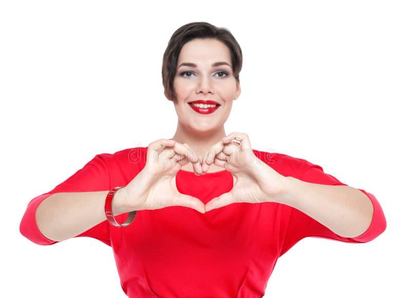 Mooi plus groottevrouw die hartvorm met haar handen doen Focu stock fotografie