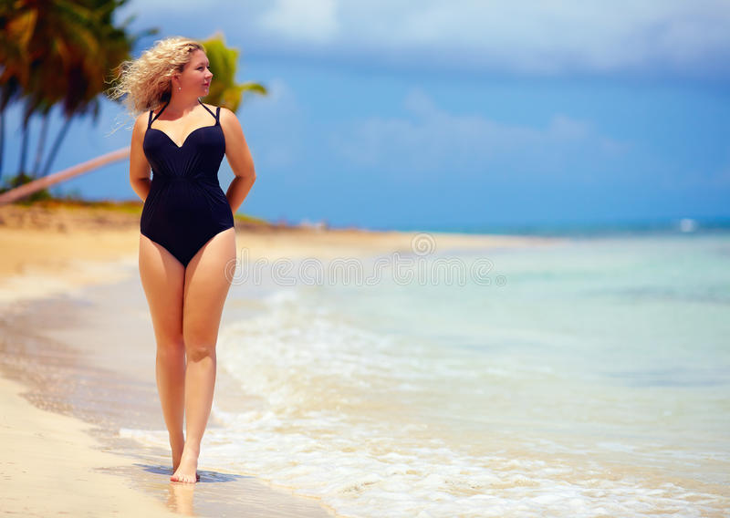 Mooi plus groottevrouw het lopen op de zomerstrand royalty-vrije stock afbeelding