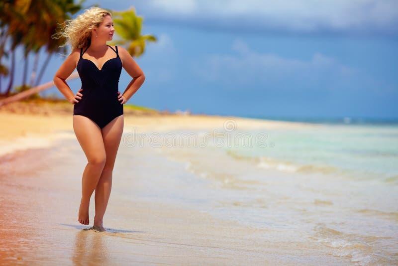 Mooi plus groottevrouw het lopen op de zomerstrand royalty-vrije stock foto's