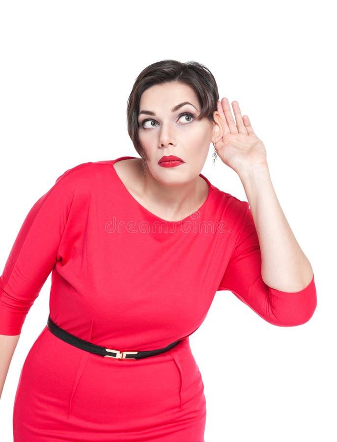 Mooi plus groottevrouw het luisteren met hand aan oorconcept stock foto