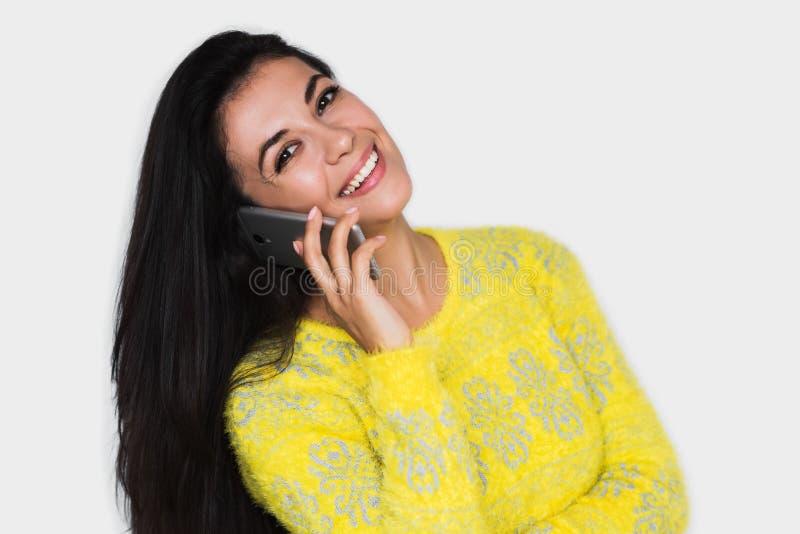Mooi portret die van aantrekkelijke jonge gelukkige vrouw met smartphone, gele sweater, met vrij toothy glimlach dragen royalty-vrije stock afbeelding