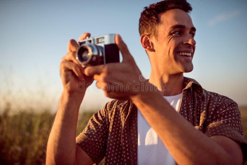 Mooi portret van de knappe glimlach jonge mens met uitstekende camera, op een weideachtergrond Reisstemming fotografie stock foto