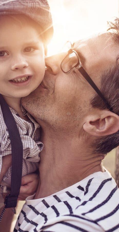 Mooi portret van een leuke kleine jongen die zijn papa koesteren royalty-vrije stock foto's
