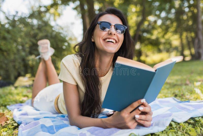 Mooi portret van een schitterende jonge donkerbruine vrouw die een boek in het park lezen Gelukkige vrouwelijke student die en a  stock afbeelding