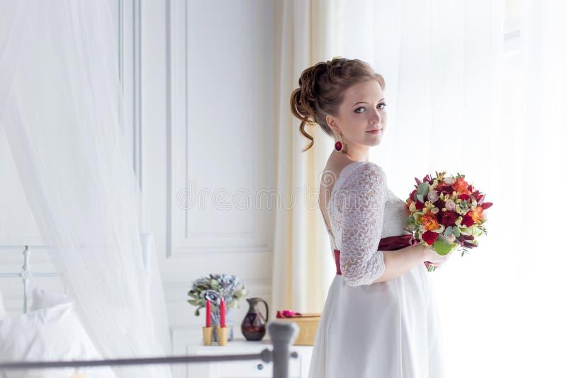 Mooi portret van een zachte leuke gelukkige bruid in een witte kleding met een helder klein gekleurd boeket stock foto's