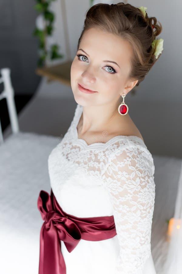 Mooi portret van een zachte leuke gelukkige bruid in een witte kleding met een helder klein gekleurd boeket royalty-vrije stock fotografie