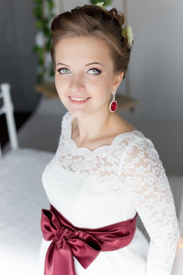 Mooi portret van een zachte leuke gelukkige bruid in een witte kleding met een helder klein gekleurd boeket stock afbeelding