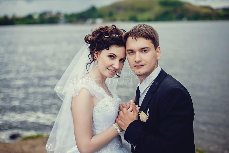 Mooi portret van gelukkige bruid en bruidegom op de achtergrond van aard Jonggehuwdenclose-up stock afbeeldingen