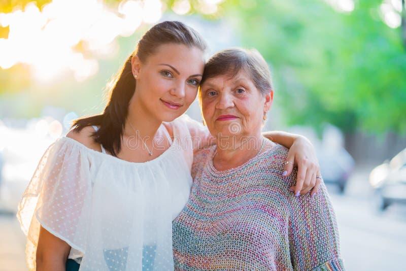Mooi portret van grootmoeder en haar kleindochter die zich openlucht op de zomerstraat bevinden Gouden uur, zongloed Meisje royalty-vrije stock afbeelding