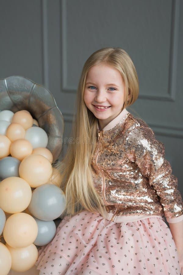 Mooi portret van het glimlachen van weinig blondemeisje in een studio met ballons royalty-vrije stock foto's