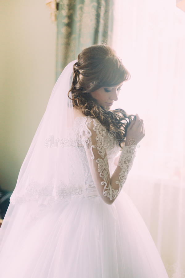 Mooi portret van jonge vrouw in witte kleding en sluier bij ochtend dichtbij venster Krullend kapsel stock foto