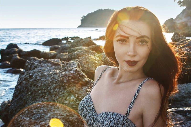 Mooi portret van leuke donkerbruine vrouw Het model van de Bohostijl Sexy model op het strand in zonsonderganglicht royalty-vrije stock foto