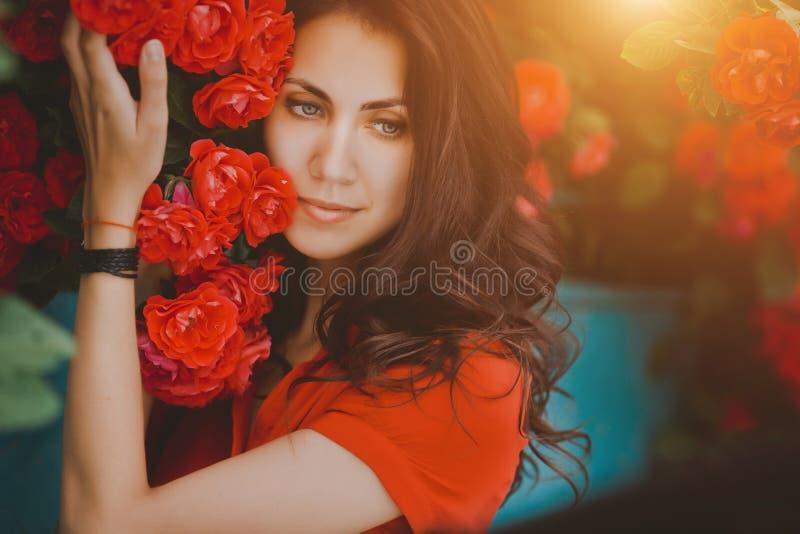 Mooi portret van sensuele donkerbruine vrouw dicht bij rode rozen Gestemd beeld stock fotografie