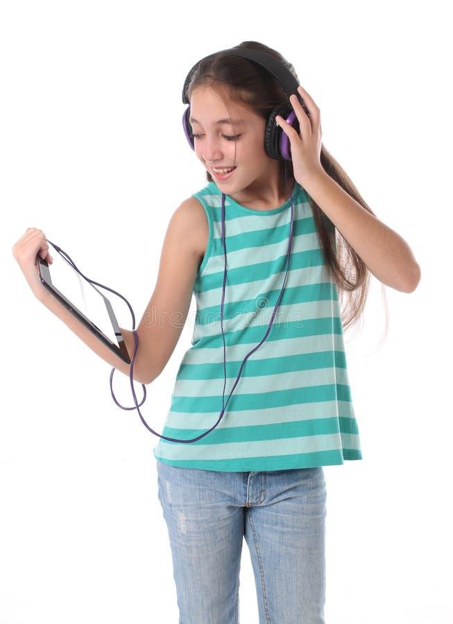 Mooi pre-tienermeisje die een tabletcomputer met behulp van stock afbeelding