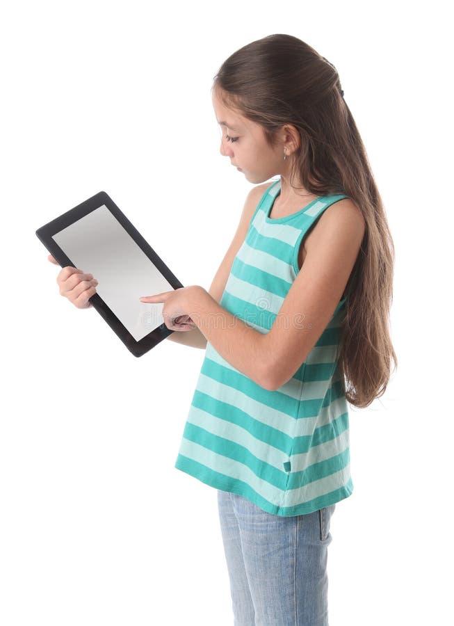 Mooi pre-tienermeisje die een tabletcomputer met behulp van royalty-vrije stock afbeelding