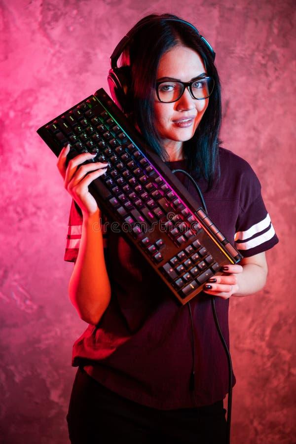 Mooi Professioneel Gamer-Meisje met Toetsenbord Toevallige Leuke Geek die Glazen en het Glimlachen dragen Cyber e-sport Internet stock afbeeldingen