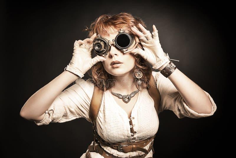 Mooi redhair steampunk meisje die over haar beschermende brillen opzij kijken stock afbeeldingen