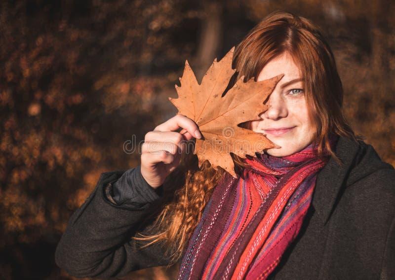 Mooi redhaired meisje met een blad stock afbeelding