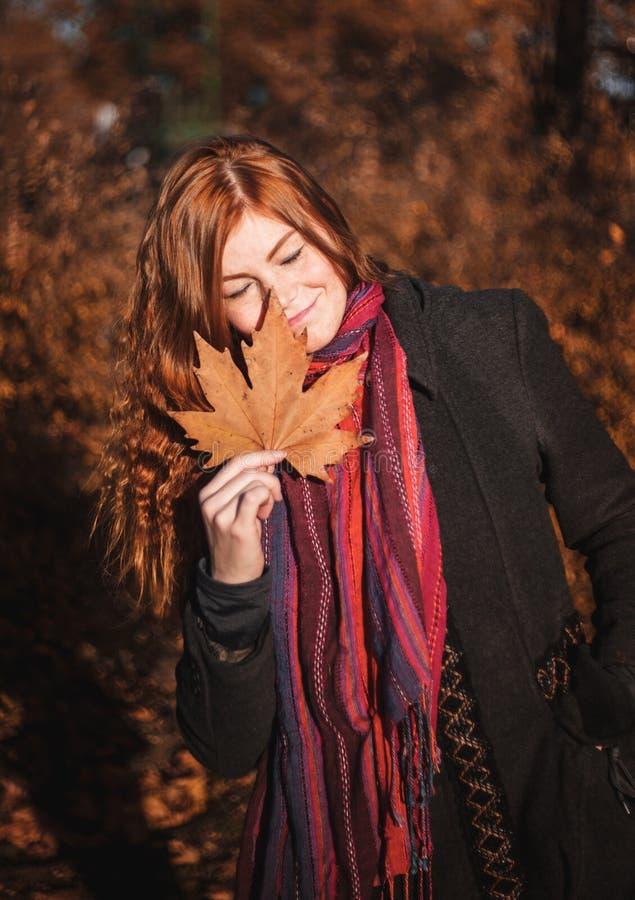 Mooi redhaired meisje met een blad stock fotografie