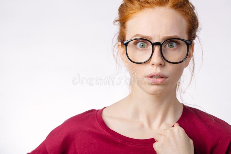 Mooi redhairmeisje die glazen dragen die met iets schokken royalty-vrije stock foto's