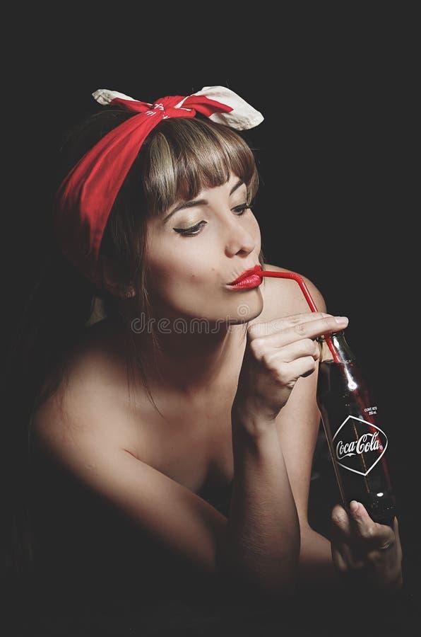 Mooi retro meisje die een oude uitstekende coca houden stock afbeelding