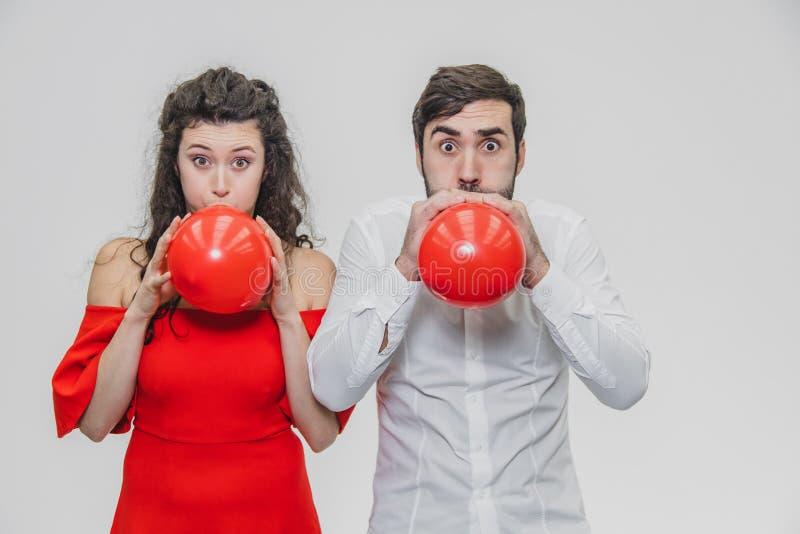Mooi romantisch die paar op witte achtergrond wordt geïsoleerd Een aantrekkelijke jonge vrouw en haar echtgenoot blazen de ballon stock foto's