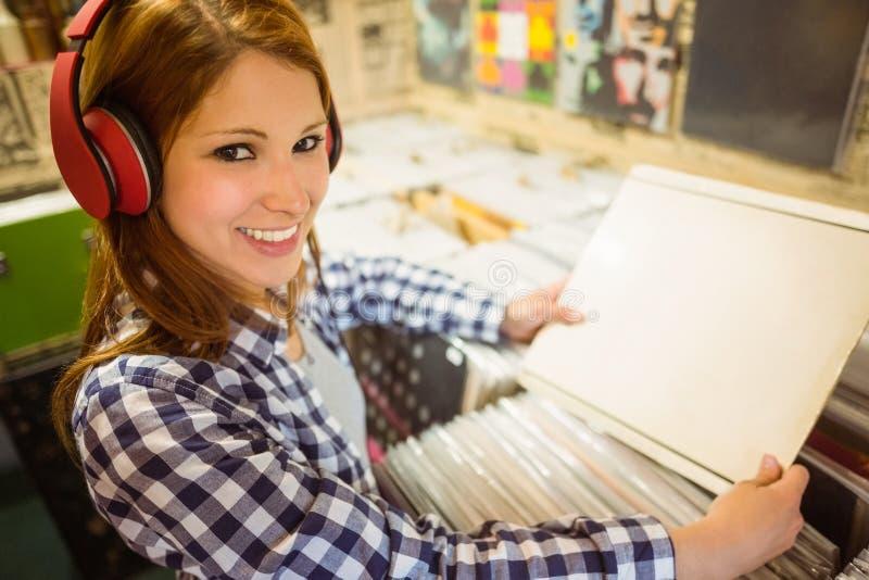 Mooi roodharige die een vinyl zoeken en bij camera glimlachen stock foto