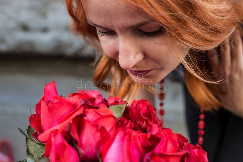 Mooi roodharige Kaukasisch meisje die kleurrijke bloemen in de tuin ruiken stock foto's