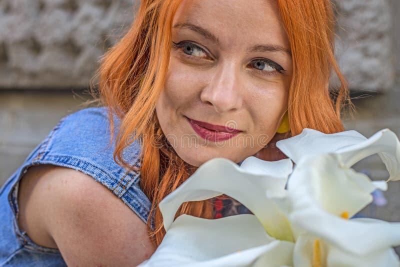 Mooi roodharige Kaukasisch meisje die kleurrijke bloemen in de tuin ruiken stock foto