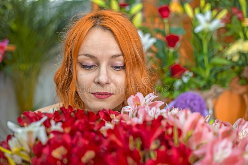 Mooi roodharige Kaukasisch meisje die kleurrijke bloemen in de tuin ruiken stock afbeelding