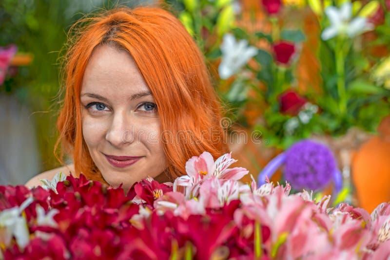 Mooi roodharige Kaukasisch meisje die kleurrijke bloemen in de tuin ruiken royalty-vrije stock foto