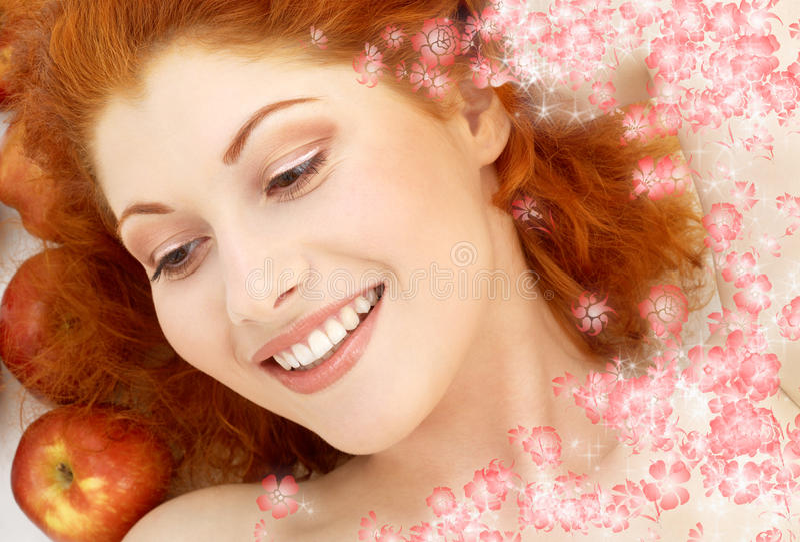 Mooi roodharige met rode appelen en bloemen royalty-vrije stock foto