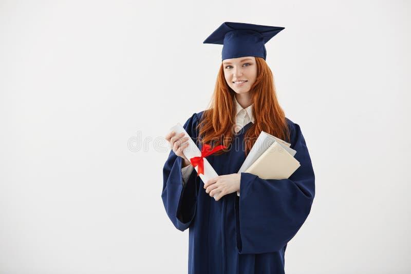 Mooi roodharige vrouwelijk gediplomeerd het glimlachen holdingsboeken en diploma over witte achtergrond stock afbeeldingen