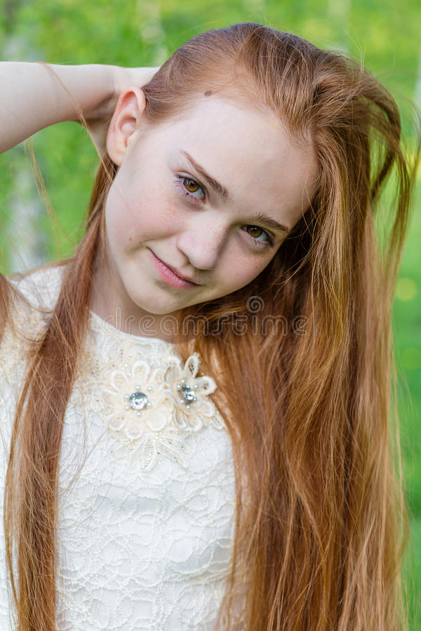 Mooi roodharigemeisje met lang haar in een park met paardebloemen royalty-vrije stock afbeelding