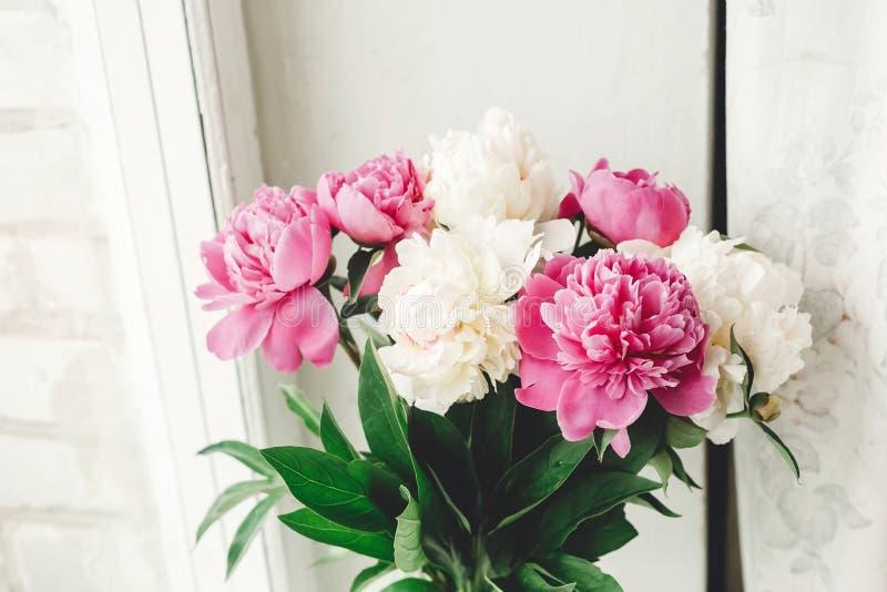 Mooi roze en wit pioenenboeket bij rustiek oud houten venster Bloemendecor en regeling Het verzamelen van bloemen Landelijk nog stock foto