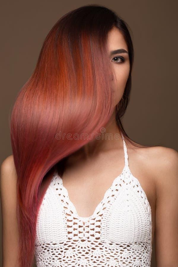 Mooi roze-haired meisje in beweging met een volkomen vlot haar, en klassieke samenstelling Het Gezicht van de schoonheid stock fotografie