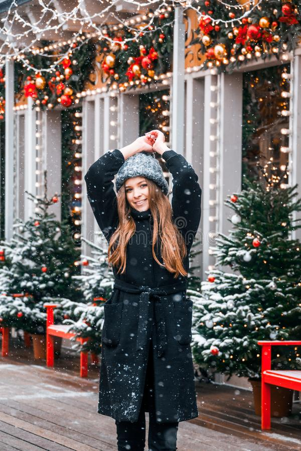 Mooi Russisch meisje in een wolkendag in de winterkleren die pret in Tverskaya-Vierkant in Kerstmistijd hebben stock afbeelding