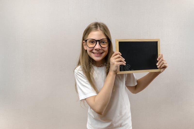 Mooi schadelijk meisje die met glazen een teken in haar handen houden Exemplaar-ruimte royalty-vrije stock afbeeldingen