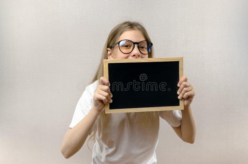 Mooi schadelijk meisje die met glazen een teken in haar handen houden Exemplaar-ruimte stock foto