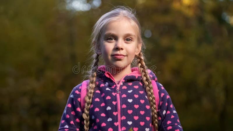 Mooi school verouderd meisje met twee vlechten die en camera glimlachen bekijken stock foto