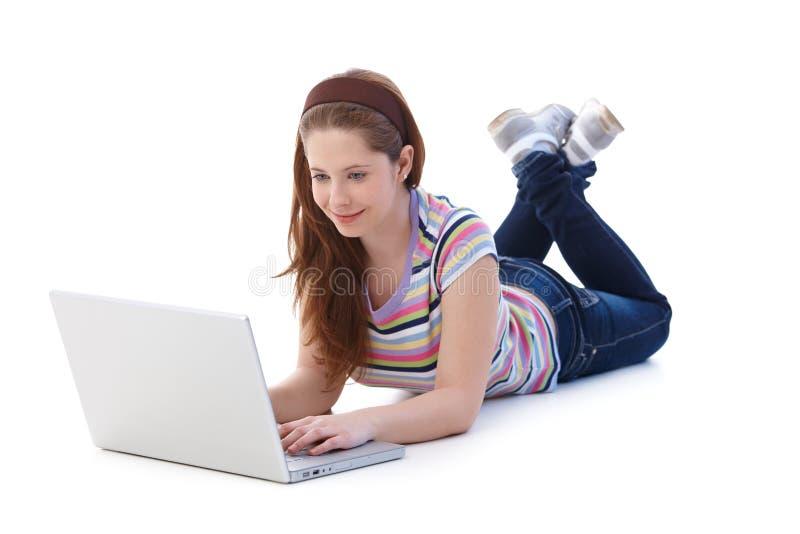 Mooi schoolmeisje dat Internet het glimlachen doorbladert stock afbeelding